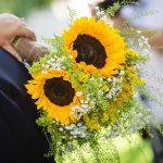 the bride holding the sunflower bouquet and hugging the groom