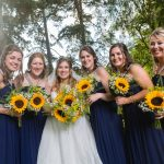 the bride and her maids holding sunflowers