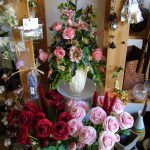 Pink and red roses next to a vase of pink flowers