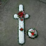 white and red flowers in the shape of a cross