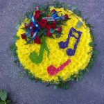 musical notes arranged on a bed of yellow flowers`