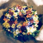 a wreath of yellow, orange, red, and purple flowers