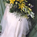 a bouquet of yellow flowers laid down on a wedding dress