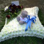 teddy bear sitting on top of a bed of flowers