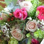 An assortment of cream and pink flowers in a vase
