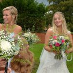 The bride and her bridesmaid smiling