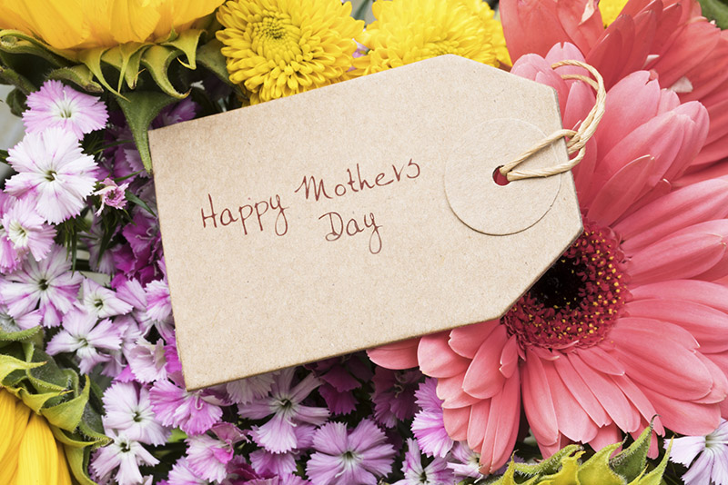 Close up of Mother's Day greeting tag on bouquet of flowers.