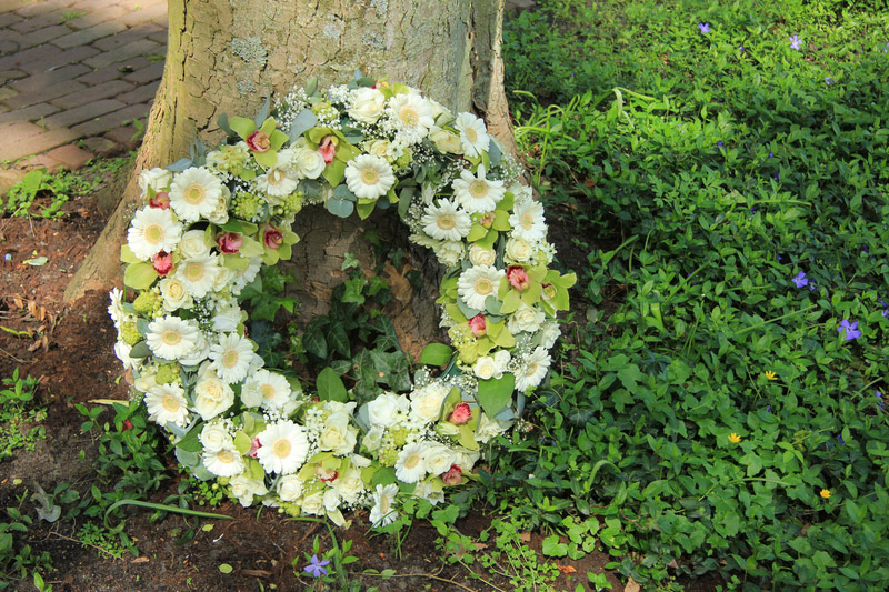 Sympathy wreath near a tree, various sorts of white flowers
